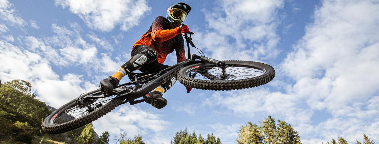 自分でデザインしたマウンテンバイクジャージを着てジャンプするマウンテンバイカー