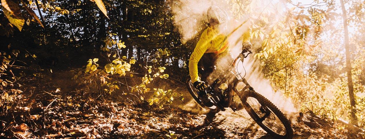 自分でデザインしたマウンテンバイクジャージを着て日差しの中森を走り抜けるマウンテンバイカー