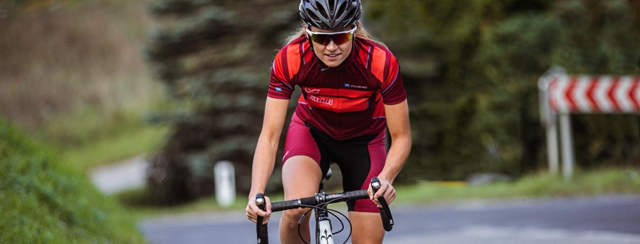 オリジナルデザインのサイクルジャージを着用しロードバイクをこぐ女性