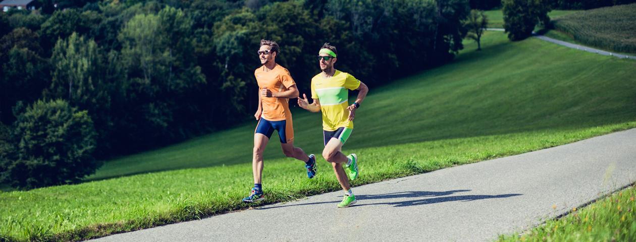 Twee joggers in kleurrijke, zelf ontworpen hardloopkleding in een straat op het platteland