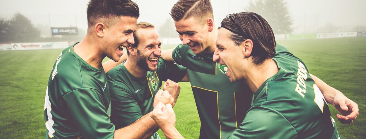Voetballers in groene zelf ontworpen voetbalshirts zijn blij