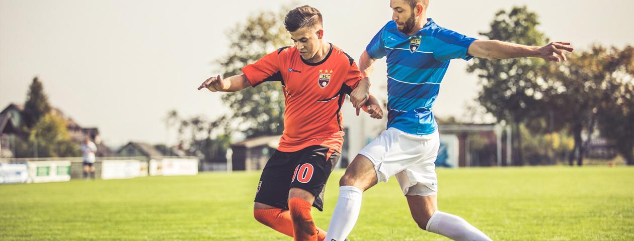Twee voetballers in duel in zelf ontworpen voetbalshirts