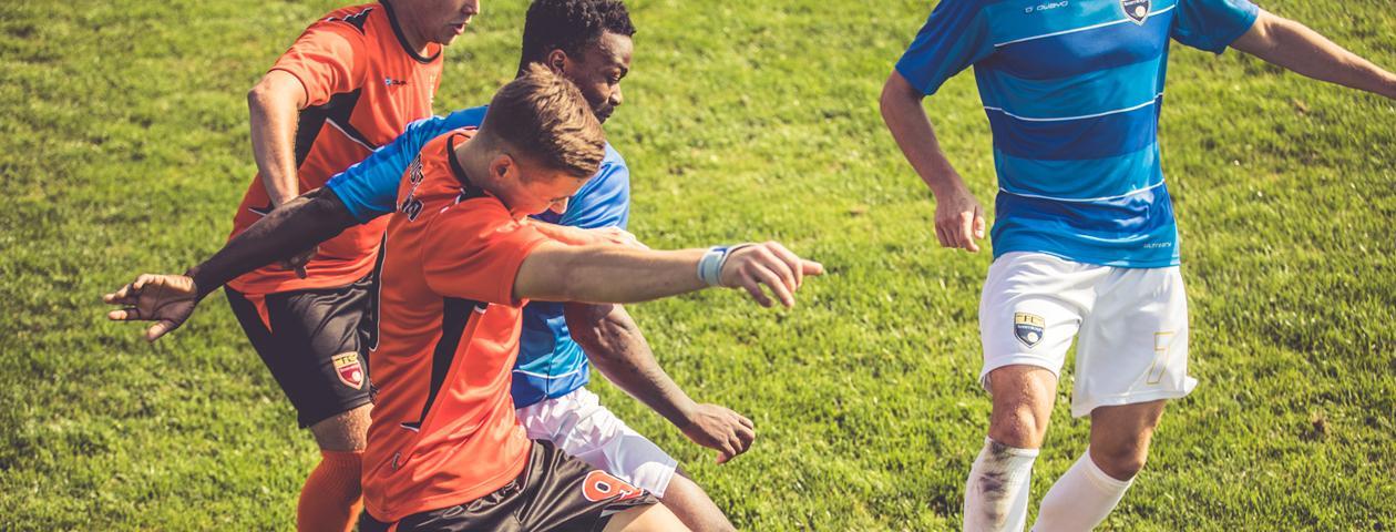 Voetbalspelers in zelf ontworpen voetbalshirts in actie