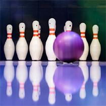 Bowlingball auf einer Bahn, der auf Bowlingpins zurollt