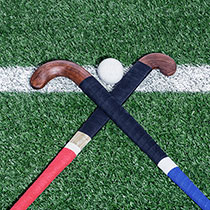 Two diagonally crossed field hockey sticks lying on a playing field. In between is a field hockey ball on one side.