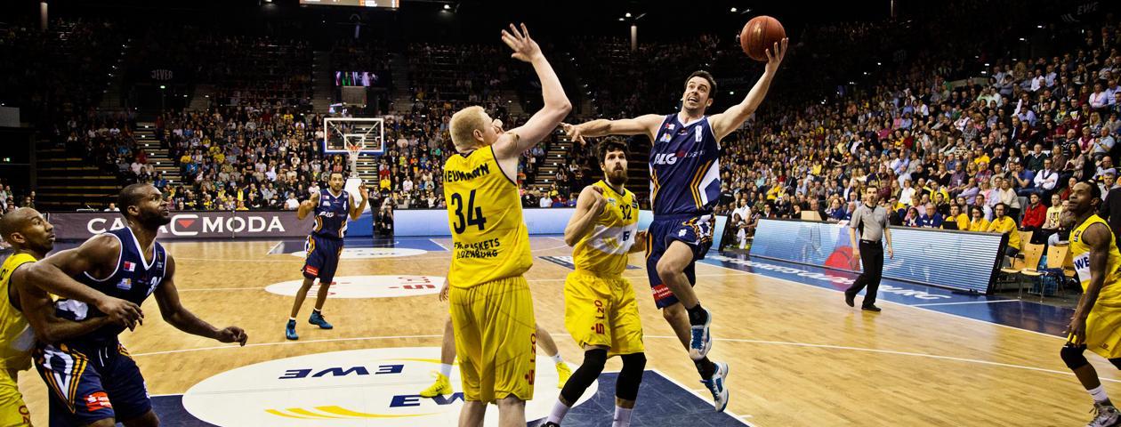 Basketteur qui attaque le panier dans un maillot personnalisé bleu et défendu par un joueur portant un maillot jaune