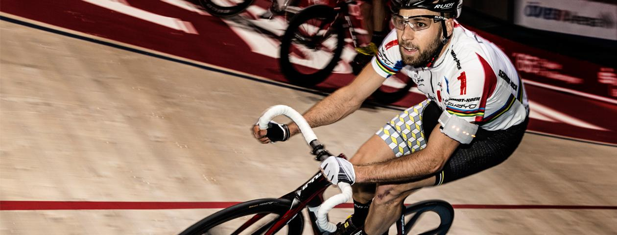 Cyclist in customized cycling jersey and bib shorts on velodrome during cycling event