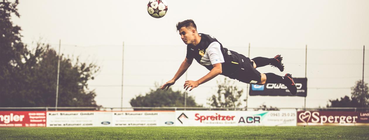 Fußballer in selbst gestaltetem schwarz-weißen Trikotsatz beim waagrechten Kopfschuss