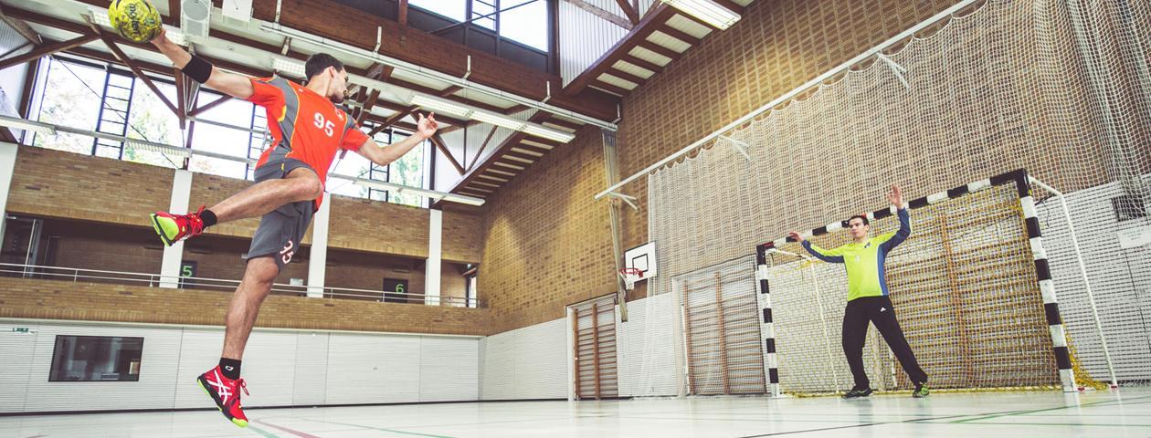 Handballer mit selbst gestaltetem orange-grauen Handballtrikotsatz wirft springend auf das Tor