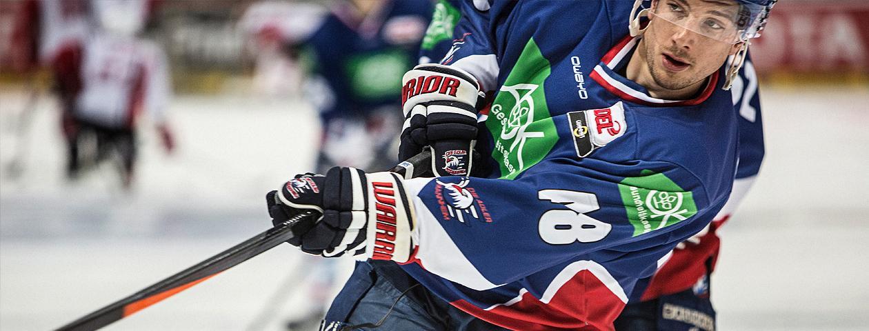 Adler Mannheim-Eishockeyspieler mit individualisiertem blauen Eishockeytrikot in Nahaufnahme