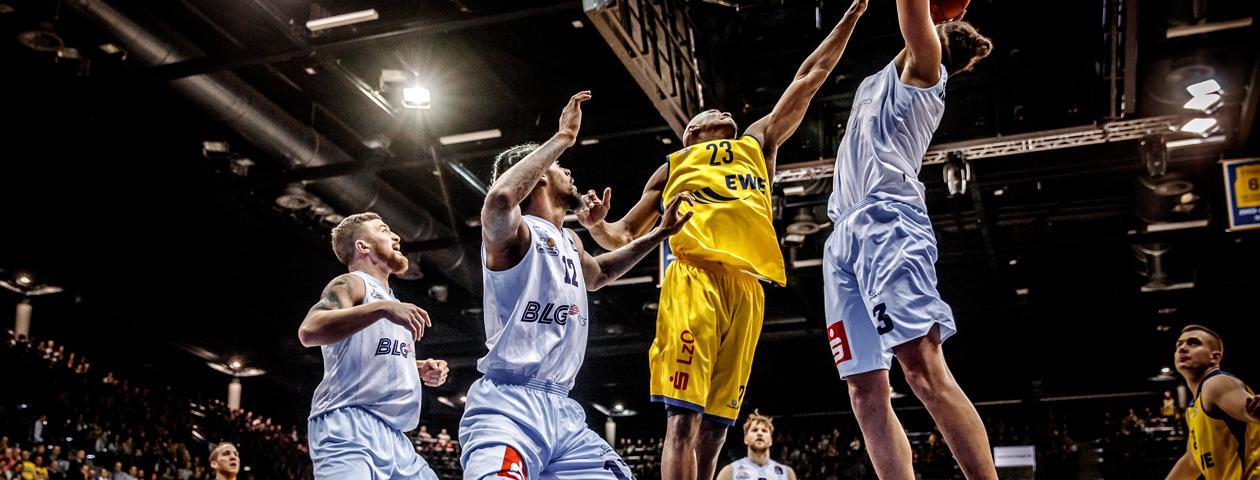 Giocatore di basket con maglia personalizzata owayo blu salta e difende la palla contro giocatori con maglia gialla.