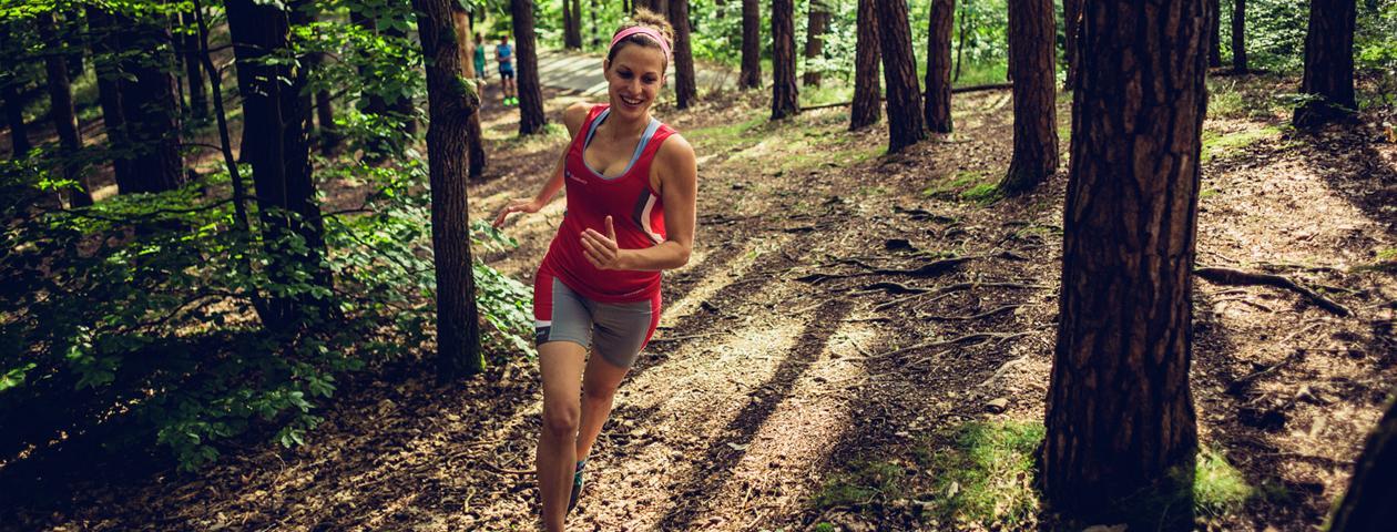 Coureuse à pied équipée d'un maillot personnalisé rouge flashy en train de courir dans les bois