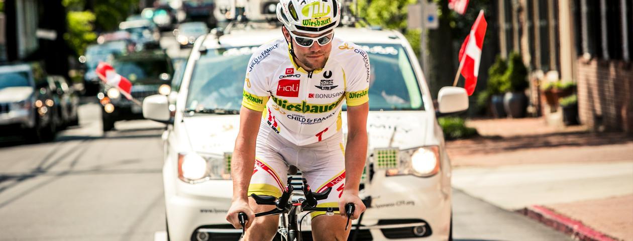 Campione di ultracycling Christoph Strasser ripreso di fronte davanti all'auto di scorta tecnica con maglia e pantaloncini personalizzati.